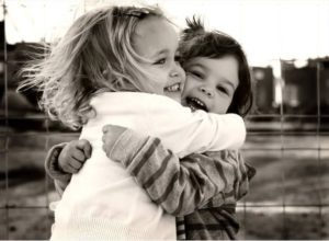 Black and white image of young children hugging adorably